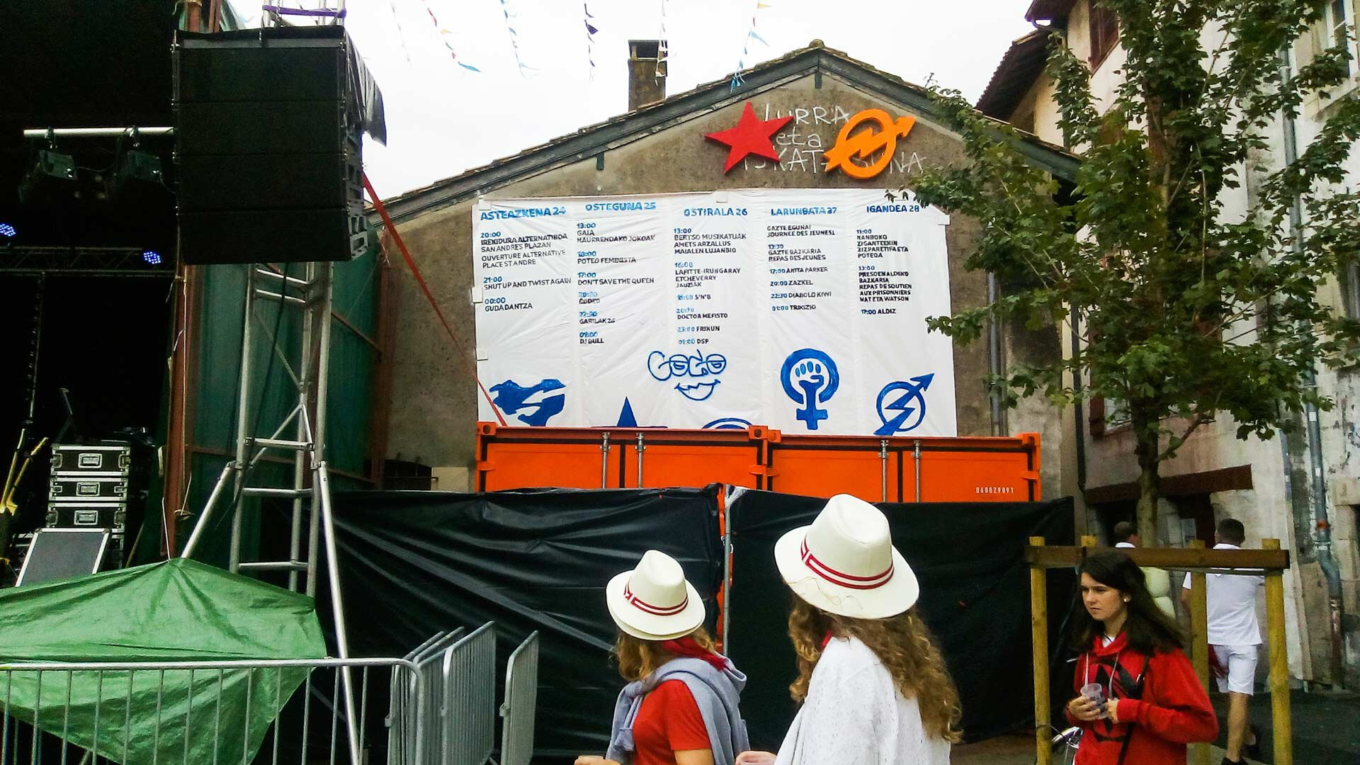 Trois personnes arrivent au festival Alternatiboak. La programmation est écrite en euskara.