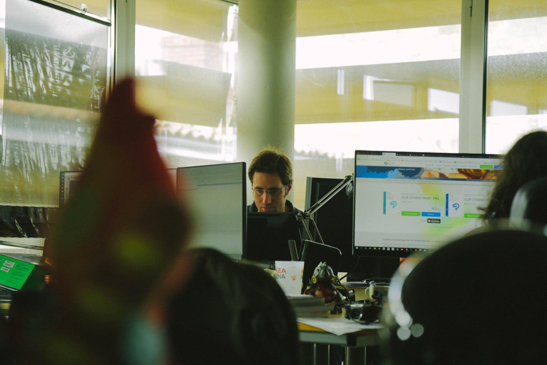 Thomas Vasseur, graphiste chez Motion Twin, derrière ses écrans.