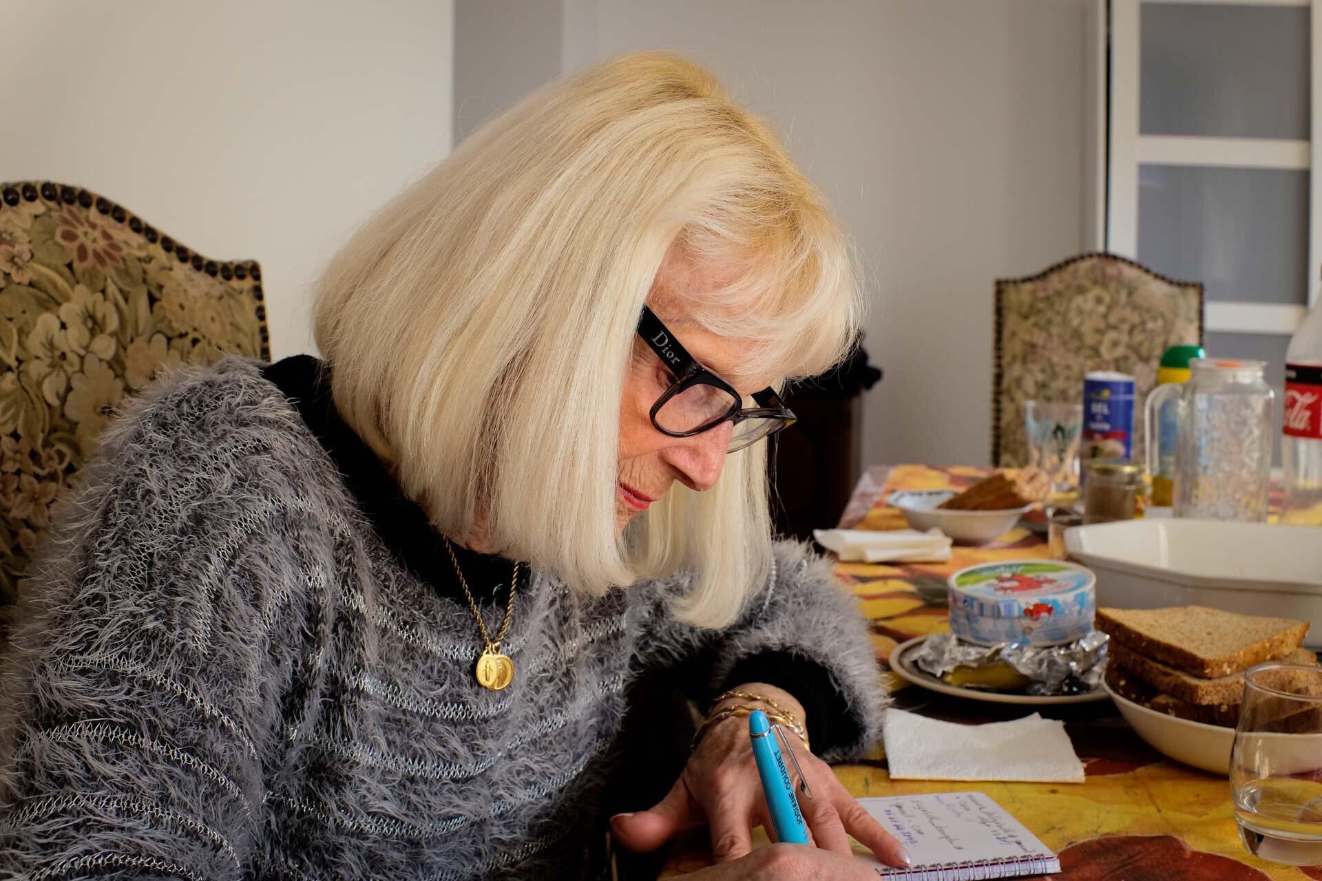 Élizabeth en train d'écrire sur sa table, dressée pour les personnes sans abri qui viendront manger.
