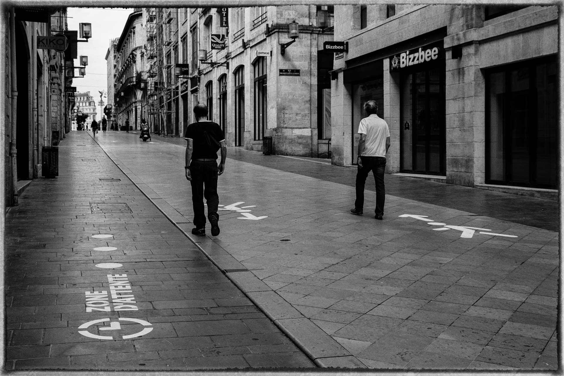 Deux personnes marchent dans la rue Sainte-Catherine, découvrant les marquages au sol pour que les piétons respectent les sens de circulation.