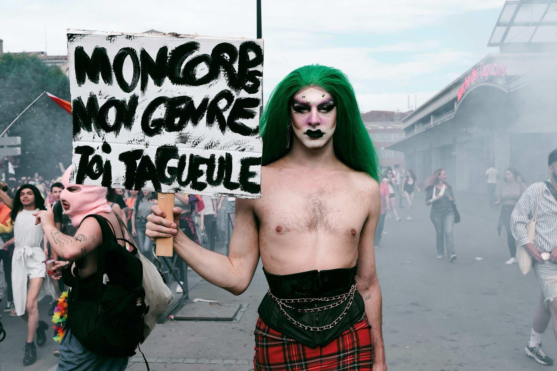 """L'artiste La Syph devant le Marché des Capucins pendant la Pride, avec la pancarte """"Mon corps, mon genre, toi ta gueule""""."""