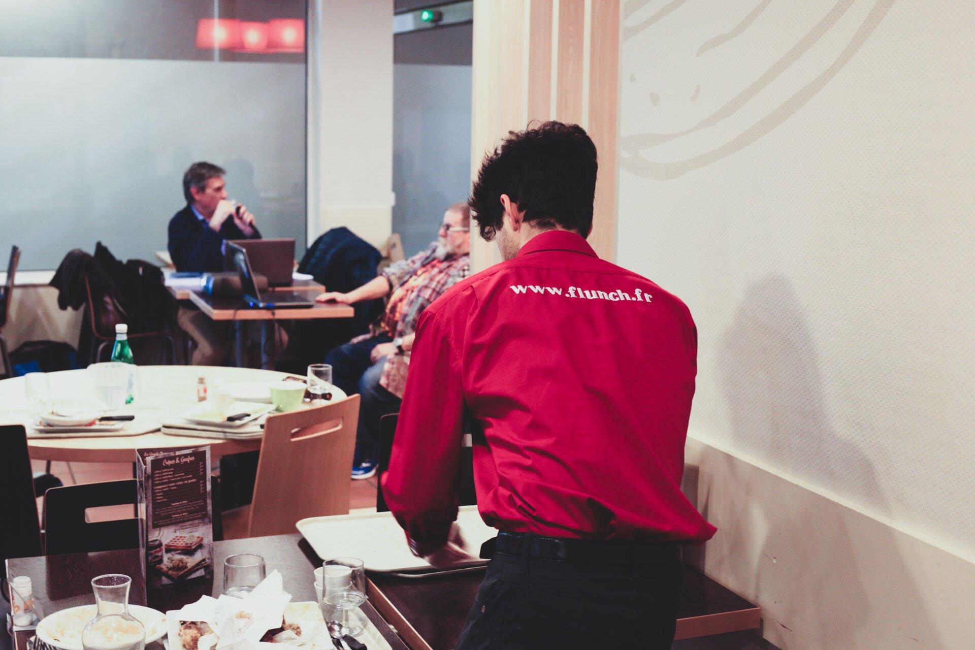 Un serveur du flunch, reconnaissable avec sa chemise rouge, retire des plateaux vides.