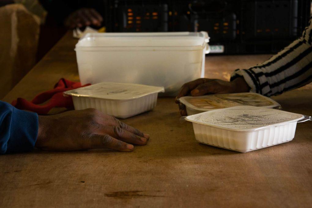 Des accueillis partagent un repas dans les locaux de Pausa